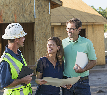 Image of people standing in front of home construction